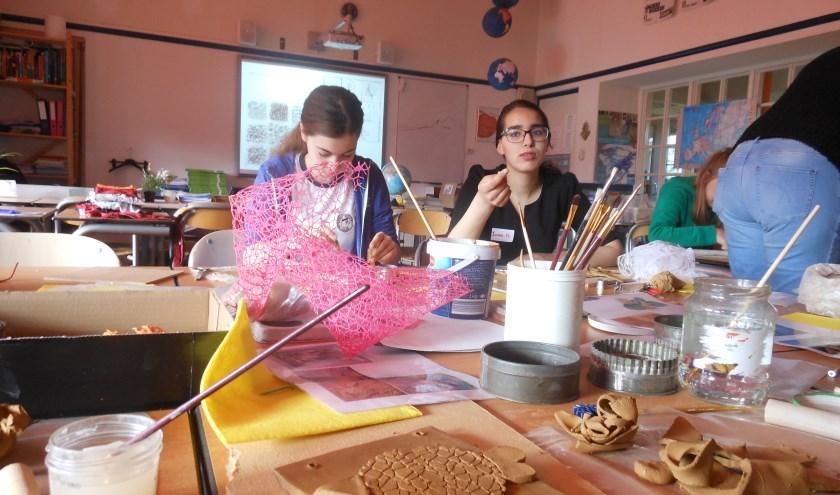Tessa en Iman maken kleifiguren.