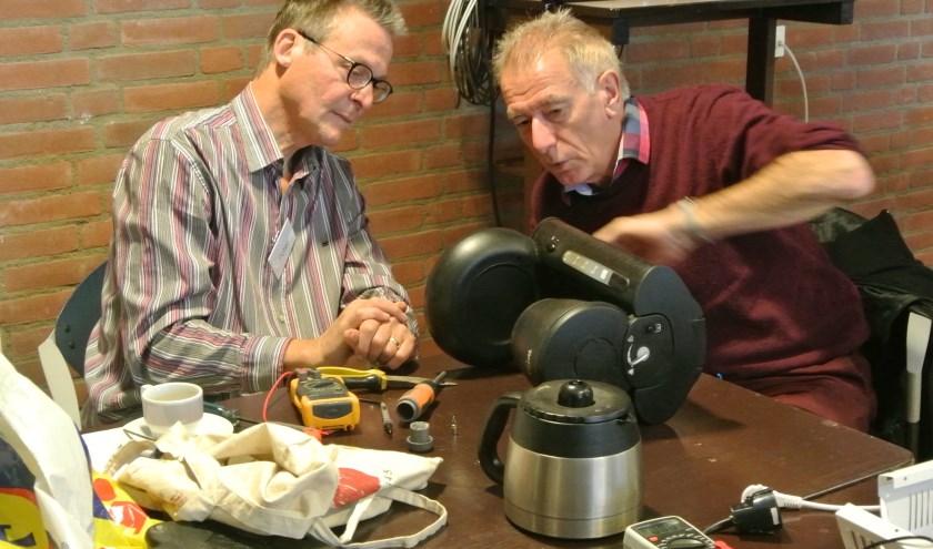 Henk Zandvliet (rechts) onderzocht zijn koffiezetter met behulp van reparateur Peter. Er bleek slechts een nieuwe zekering nodig om het apparaat weer te laten werken.