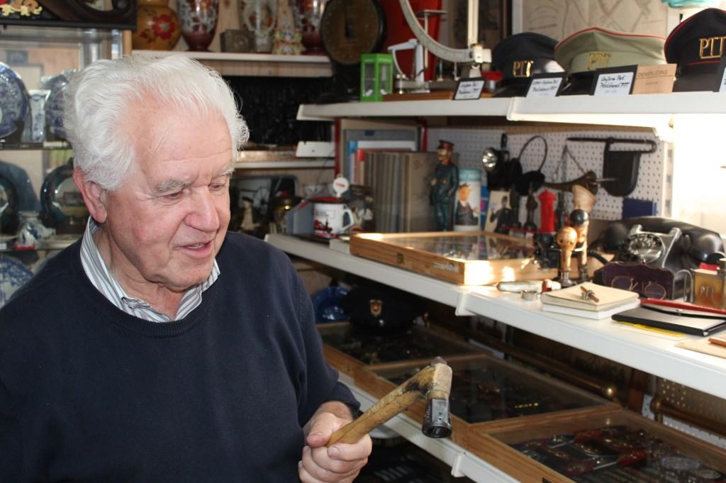 Theo Schouten in zijn mini-ptt-museum met een stempel waarmee voorheen brieven e.d. met de hand gestempeld werden.  © De Vierklank