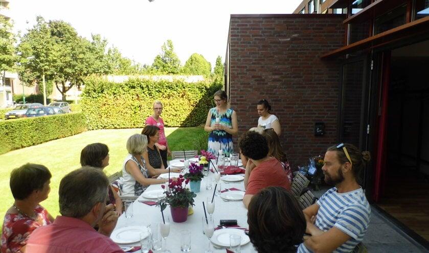 Christine Thomas (staand midden) heet de aanwezige welkom op de viering van het eenjarig bestaan van het Maatjesproject Samen Oplopen.
