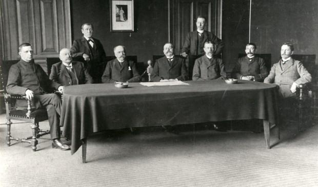 Een foto van de gemeenteraad van 1909 -1911, allen in stemmige kleding poserend. Zittend v.I.n.r. S. Floor (1900-1911) r.lid; Jhr. Mr. D. de Blocq van Haersma de With (1879-1907) burgerm. en (1882-1915) r.lid; M. v. Marwijck Kooij (1895-1913) r.lid; H. Ph. J. baron  van Heemstra (1907-1927) burgem.; Mr. J.E.W. Twiss (1887-1917) r.lid.; P.N. Hoogland (1905-1931) r.lid; C.L. baron van Boetzelaer (1900-1931) r.lid. Staand (l) T. Meijer (1900-19  © De Vierklank