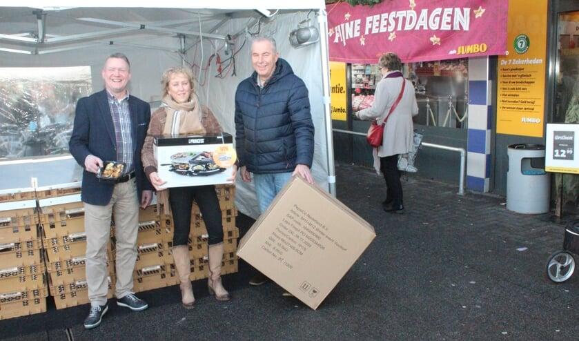 Jelle Farenhorst (l) maakt Hester Schouten en Wim van Keulen blij met een prijs.