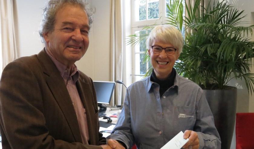 Wethouder Rost van Tonningen ontvangt een exemplaar van het jaarverslag en werkplan van VVN-voorzitter Enny Doornenbal.