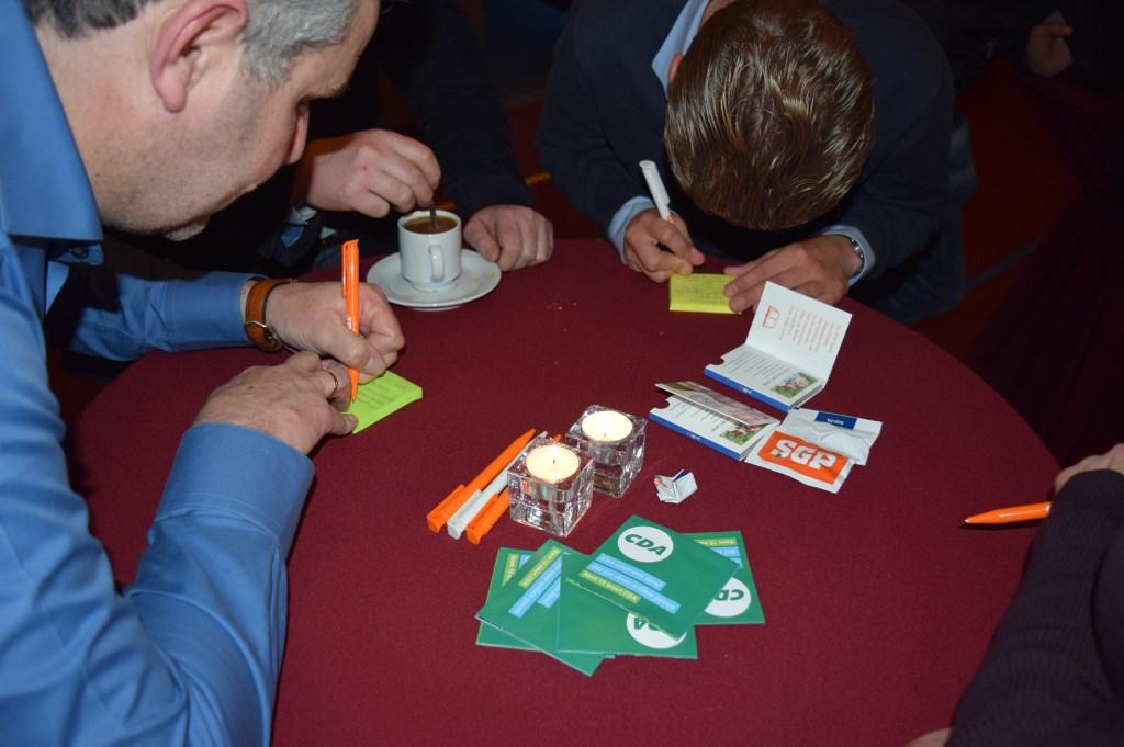 Bezoekers schrijven hun stelling op een post-it en leveren daarmee een bijdrage aan het verkiezingsdebat.  © De Vierklank
