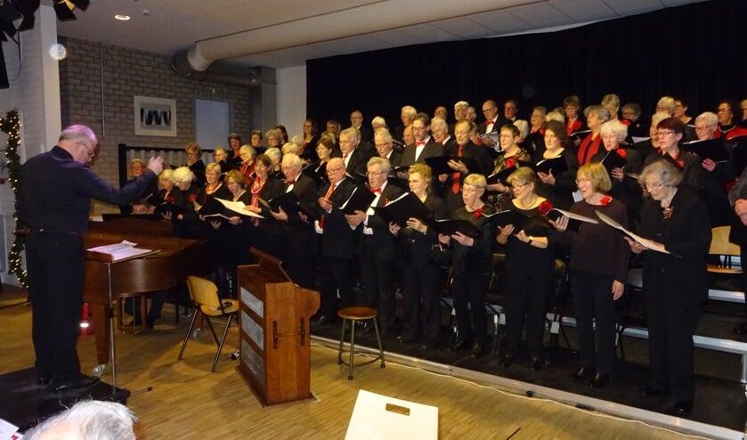 Een goed gevulde zaal geniet van de vocale prestaties van beide koren.