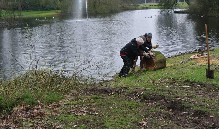 Vrijwilligers brengen de restanten van een omgewaaide boom op het droge.