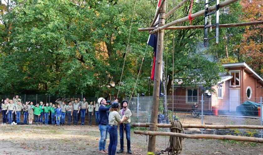 Burgemeester Sjoerd Potters helpt bij het hijsen van de vlag.