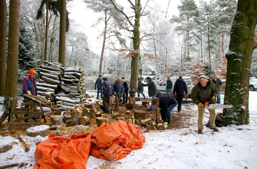 Leden van de Lions Club hakken in de sneeuw in het Ridderoordse Bos. Foto: Picasa © De Vierklank