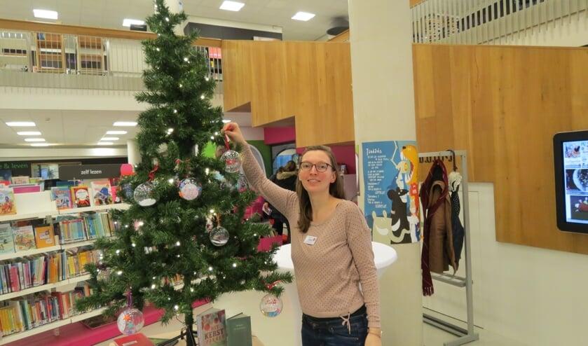 Andrea Geltink tuigt de Joris kerstboom op in de Bilthovense bibliotheek. [foto Guus Geebel]