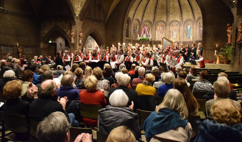Een volle kerk applaudisseert voor de muziek van de twee koren en het brandweerorkest. [foto Walter Eijndhoven]
