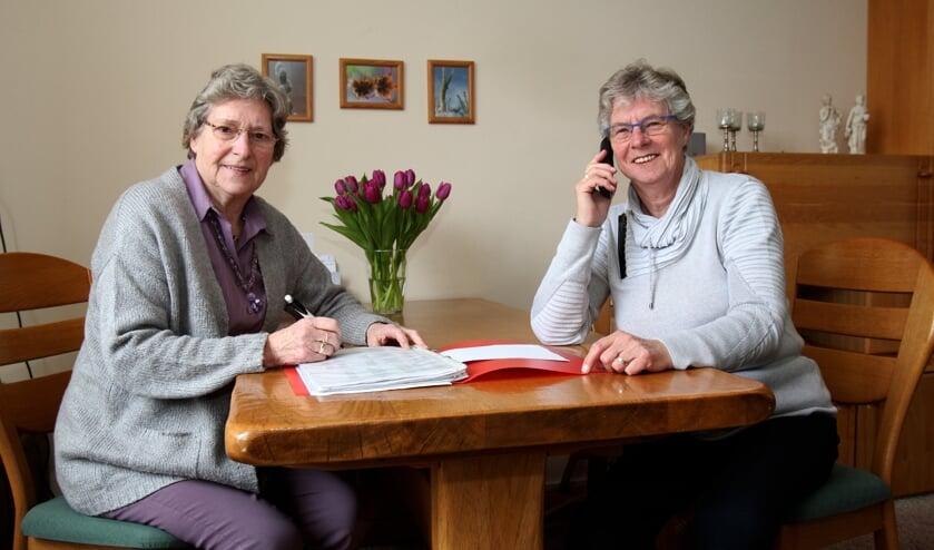 Trijnie Spoelstra en Boukje Andringa (r) zijn druk met de telefooncirkel.