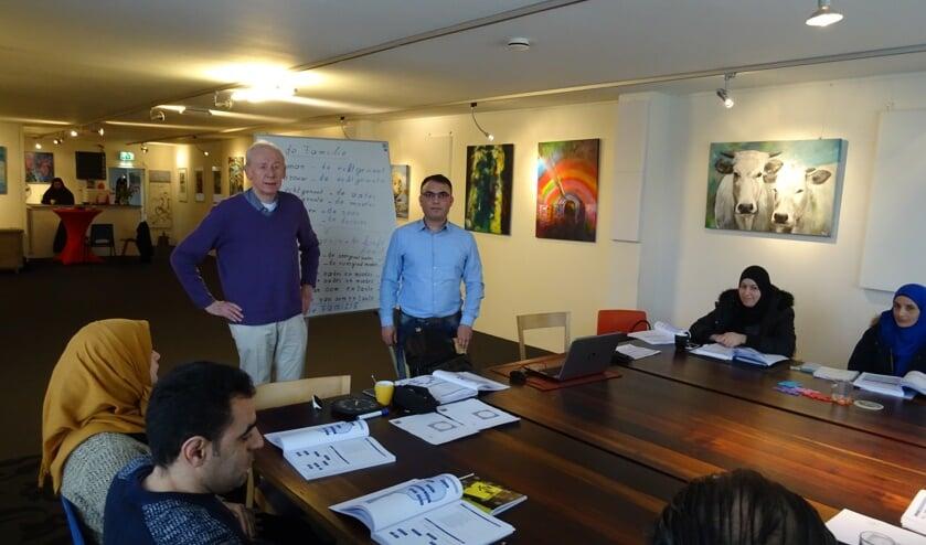 Murtada Al Hariri staat rechts naast het bord voor de klas waar Nederlandse les wordt gegeven aan Syrische statushouders. Links naast het bord docent Hans van der Lugt.