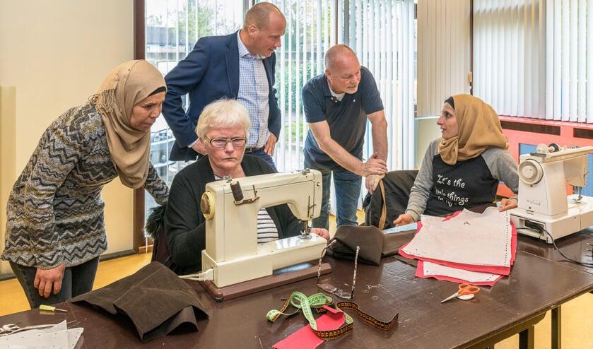 V.l.n.r. cursist Subhia Hedxishekho (krijgt uitleg over het gebruik van de naaimachine door) docent Wil Moget, Martijn van Veenendaal van Sympany en Ruud Jansen van WVT vragen cursist Walaa Awad hoe de eerste les gaat.