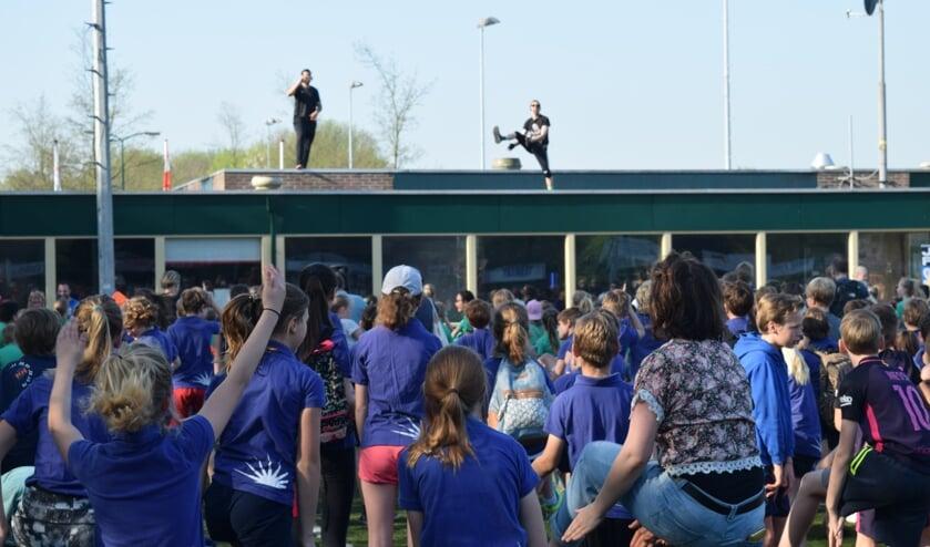Vanaf het dak van het clubhuis van FC De Bilt worden de leerlingen aangemoedigd voor de warming-up.