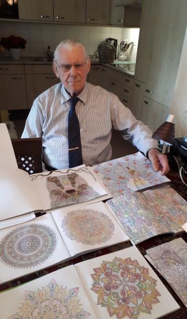 Gert Mulder toont enkele van zijn kleurtekeningen.