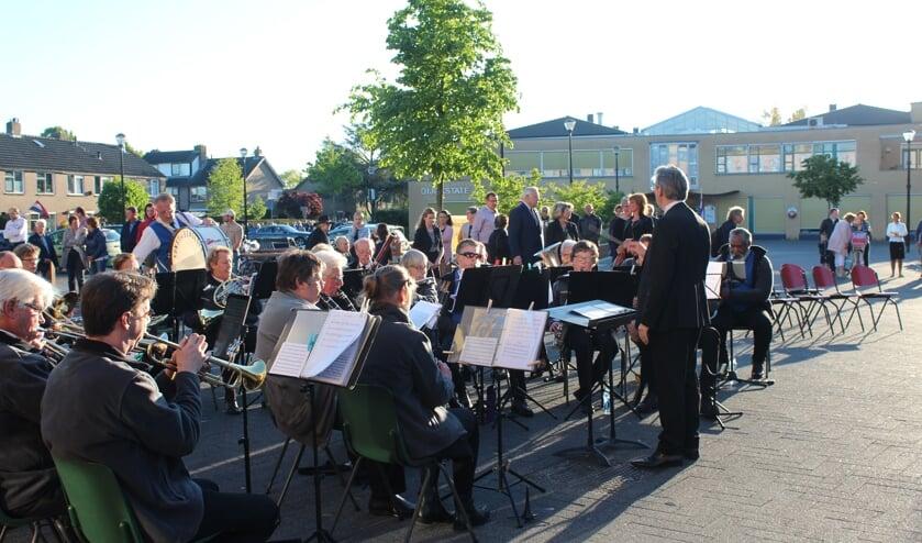 Het gezelschap bereikt het Maertensplein, waar muziekvereniging Kunst en Genoegen bij de vlag koralen speelt.