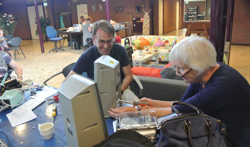 De vrijwilliger en de eigenares genieten ervan dat het apparaat weer werkt.