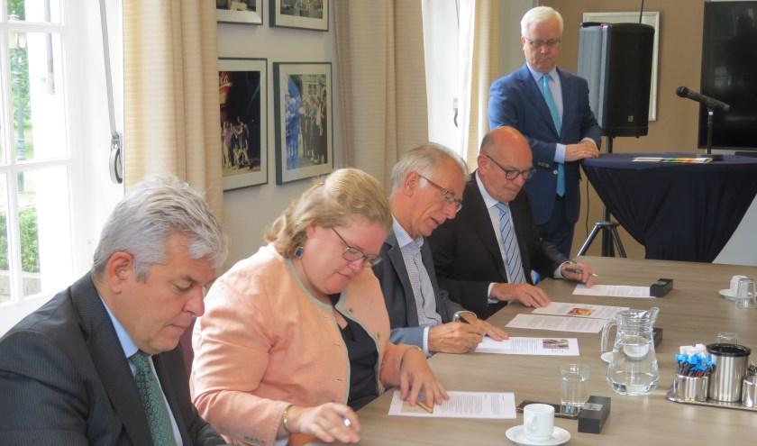 De ondertekening van het akkoord. V.l.n.r. Werner de Groot (CDA), Donja Hoevers (D66), Henk Zandvliet (GroenLinks), Fred van Lemmen (VVD) en formateur Eric Balemans.