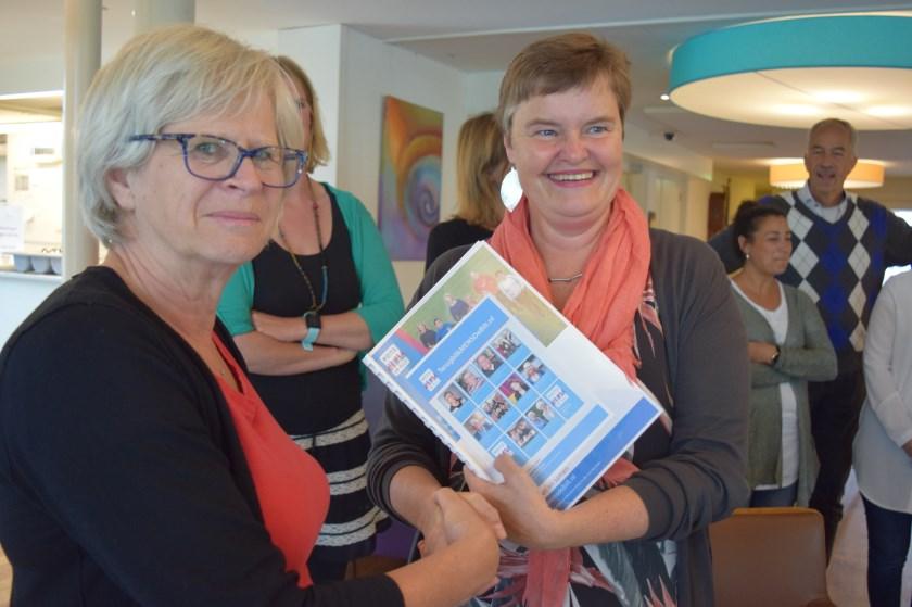 Evelien Ribbens reikt Anne Brommersma het verslag aan.