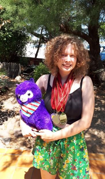 Julia met haar prijzen en de mascotte van de WSC: een Alpaca.
