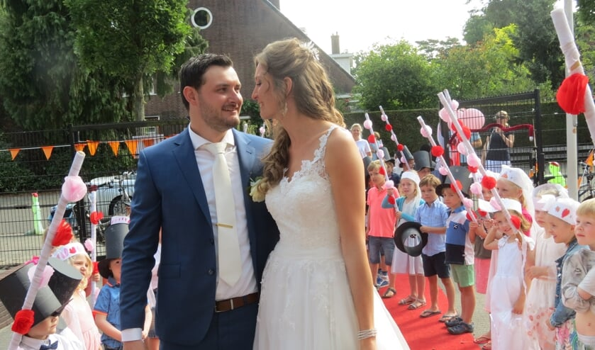 Het bruidspaar wordt door alle groepen van de school enthousiast verwelkomd en toegejuicht.