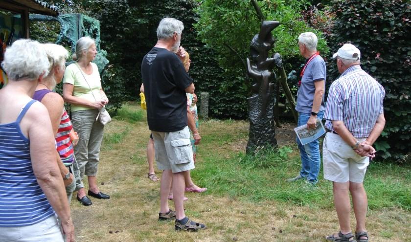 Vrijwilligers van de Stichting Jits Bakker Collectie geven uitleg over een beeld.