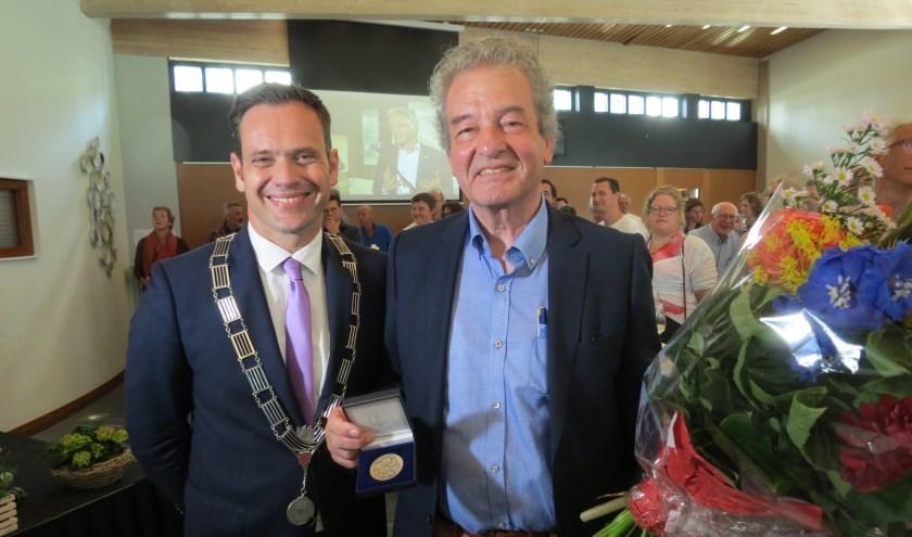 Burgemeester Sjoerd Potters reikt Ebbe Rost van Tonningen de Chapeaupenning van de gemeente De Bilt uit.