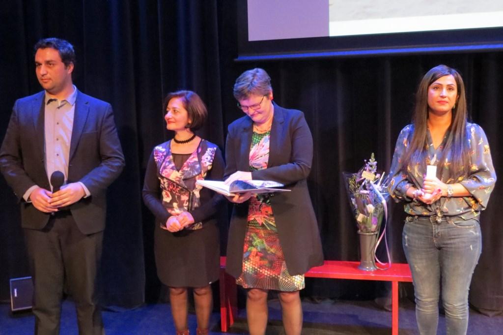 Saber Alizai, Nariné Khenkikian en Parisa Rostami bij de uitreiking van het jubileumboek aan wethouder Anne Brommersma.  © De Vierklank
