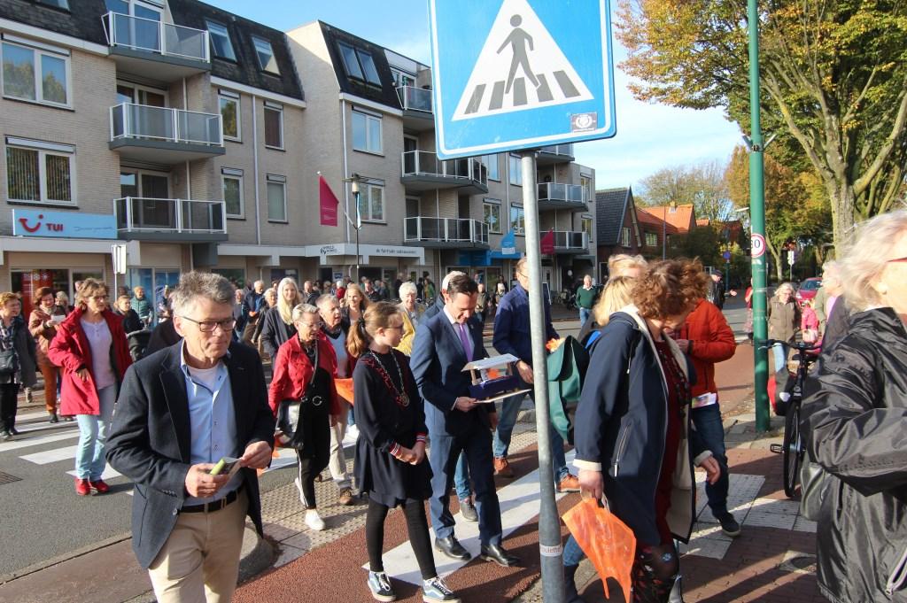 Medewerkers van de Wereldwinkel en de vele belangstellenden worden al zingend naar de nieuwe locatie op de Hessenweg begeleid.   © De Vierklank