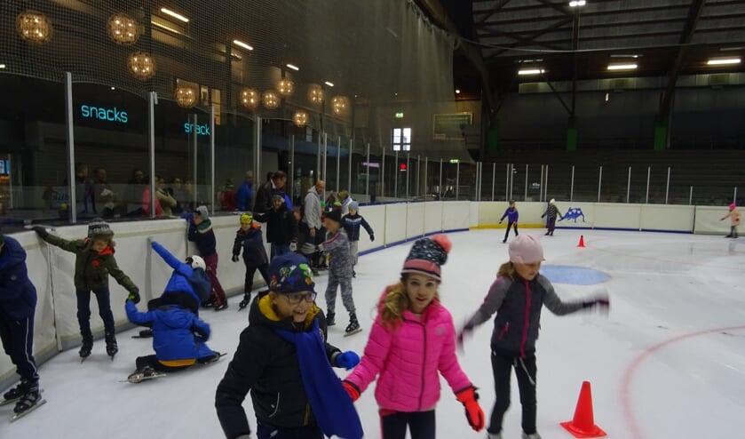 Voorzichtig proberen de kinderen hun eerste slagen te maken op het ijs.