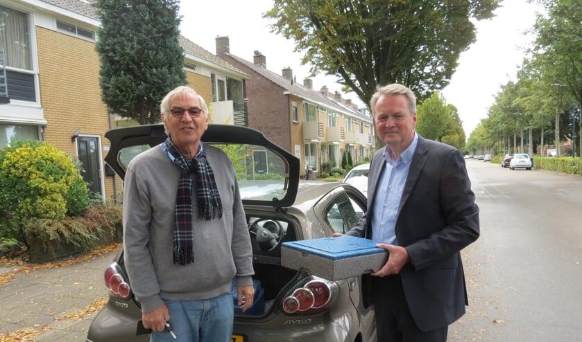 Jaap Dieben en André Landwehr (rechts) bezorgen een warme maaltijd.