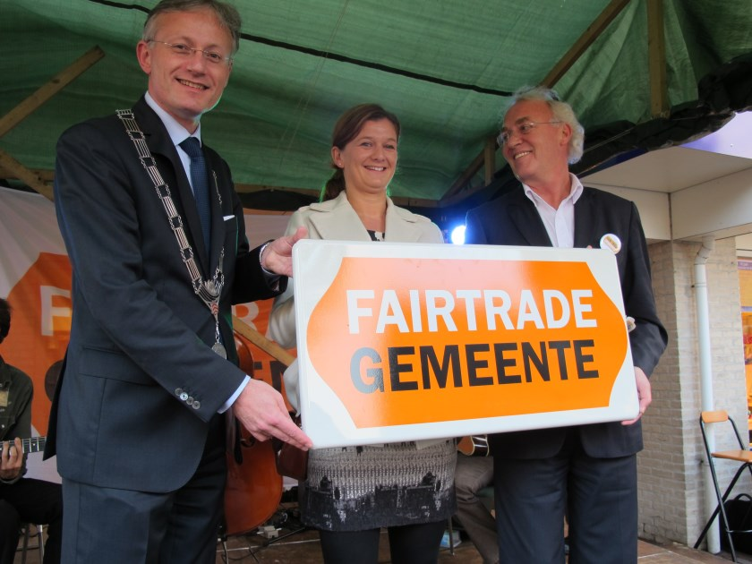 Een foto uit 2011, waarbij Liesbeth Gort (jurylid van Fairtrade Campagne Nederland) het bord Fairtrade Gemeente overhandigd aan voormalig burgemeester Arjen Gerritsen en voormalig wethouder Herman Mittendorff. [foto Lilian van Dijk]