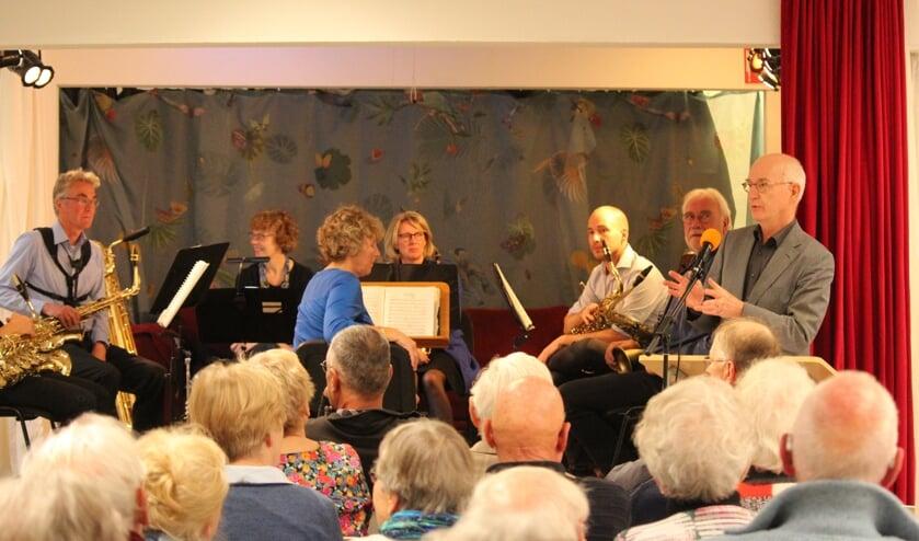Een volgepakte zaal en het Biltse saxofoonkwartet luisteren naar Martien Brinkman tijdens de inleiding over zijn boek 'Grote Woorden'.