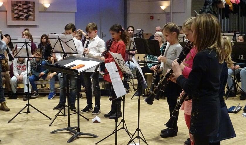 Geconcentreerd spelen de kinderen van de klarinetgroep hun oefennoten voor zij met het harmonieorkest gaan spelen.