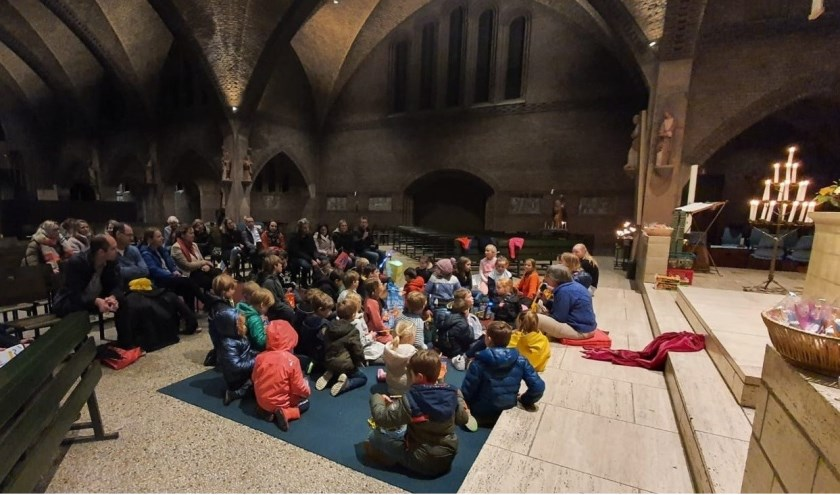 Ouders en kinderen luisteren geboeid naar het verhaal van Sint Maarten.
