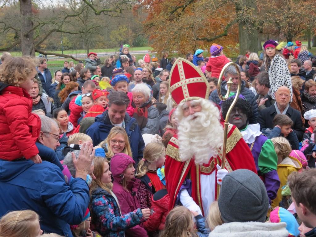 Na zijn aankomst baant de Sint zich een weg door de enthousiaste kinderen.  © De Vierklank