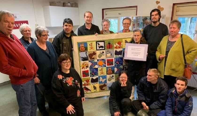 Grietje Rutgers ontvangt de quilt en Dos Schaafsma van de Kinderboerderij De Schaapskooi de cheque