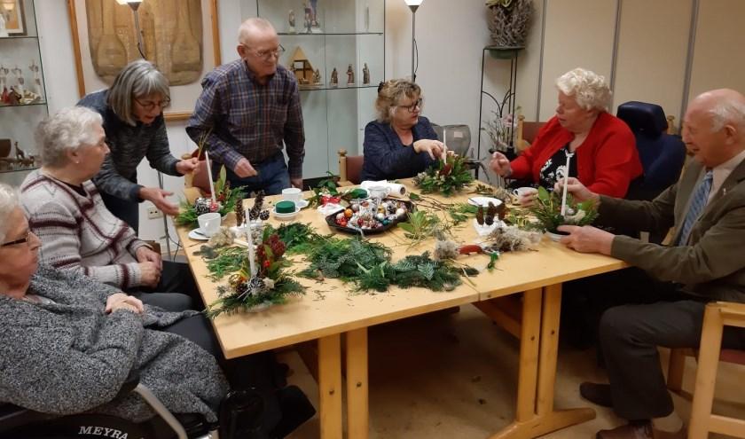 Zonnebloemgasten maken zelf een kerststukje.