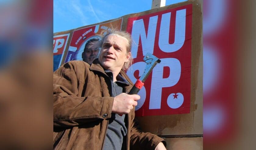 Gemeenteraadslid Menno Boer plakt en niet op een van de verkiezingsborden in de gemeente.