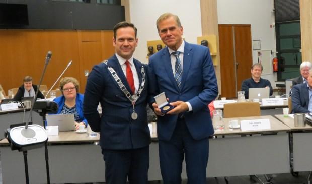 Burgemeester Sjoerd Potters reikt Han IJssennagger de Chapeaupenning van de gemeente De Bilt uit.  © De Vierklank
