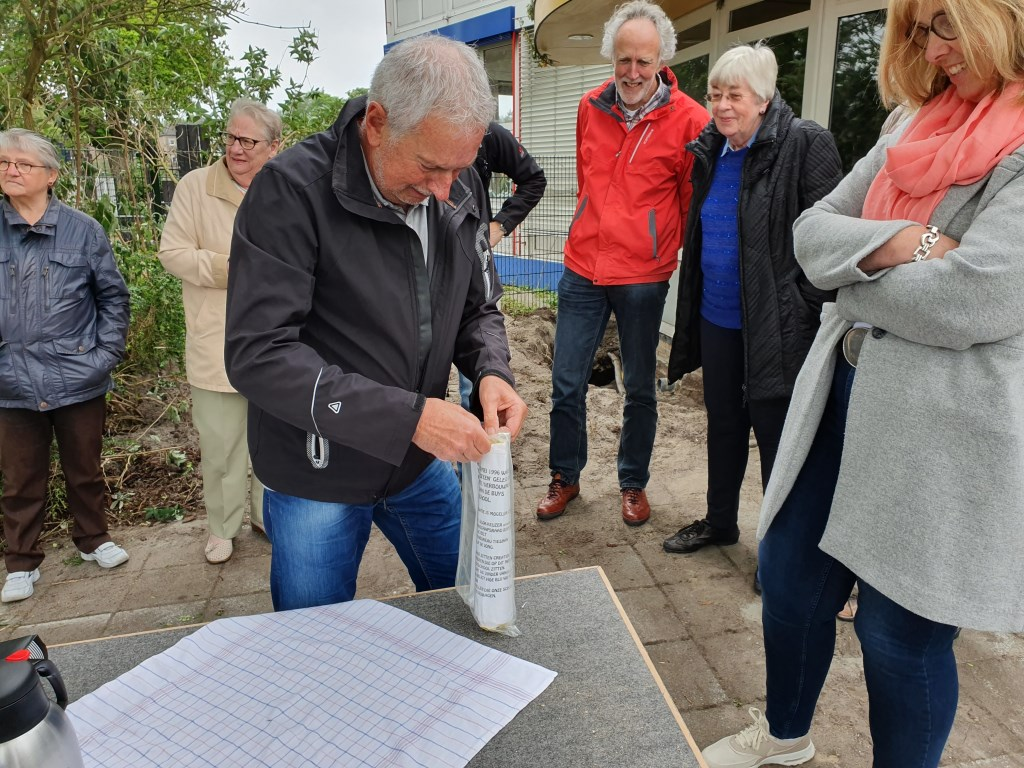 Onder toeziend oog van o.a. Wim Ruiterkamp en Truus te Pas opent Henk Smits de tijdcapsule.  © De Vierklank