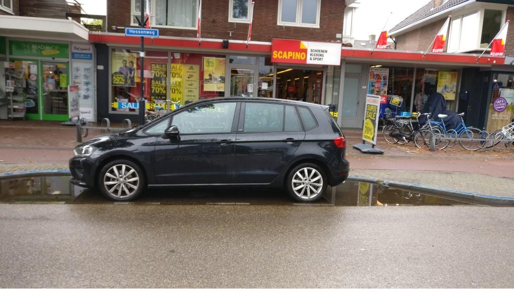 Parkeerplaatsen op de Hessenweg staan lang nadat het geregend heeft nog onder water omdat de afvoer niet goed werkt.  © De Vierklank