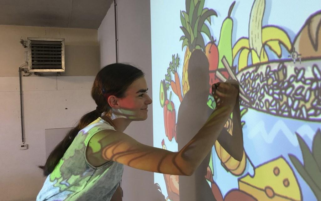 Norah Eits tekent haar ontwerp op de muur. Foto: JAN DEN OUDENMAARTENSDIJK © De Vierklank