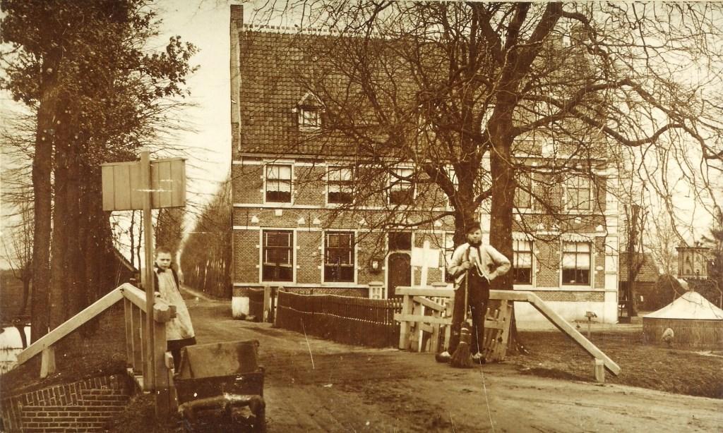 Het gemeentehuis nog zonder de in 1930 gebouwde bodewoning met op de brug links een dochter van Gart Meijers en rechts Wijn van Eekeren.  © De Vierklank