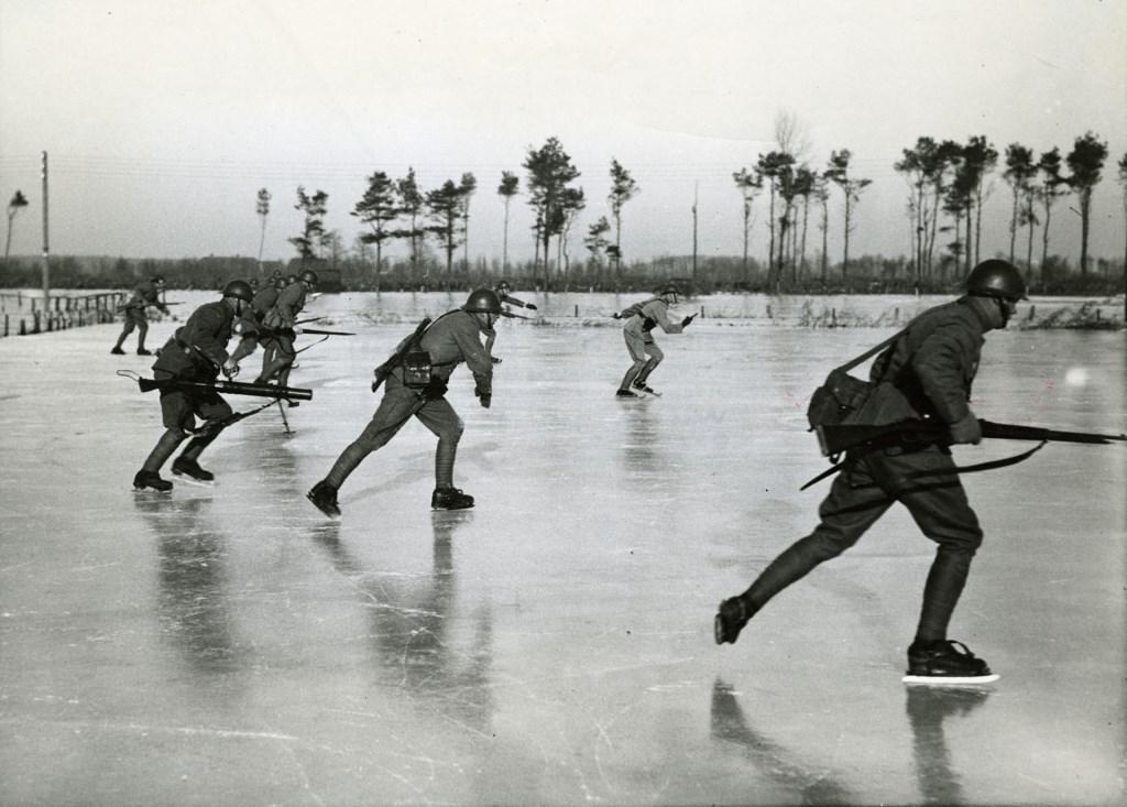 Januari '40. Nederlandse militairen gedurende de mobilisatie. Ze schaatsen hier op inundatie-ijs. (bron Co Zeijlemaker (Polygoon)/ Nederlands Instituut voor Militaire Historie, Den Haag)  © De Vierklank