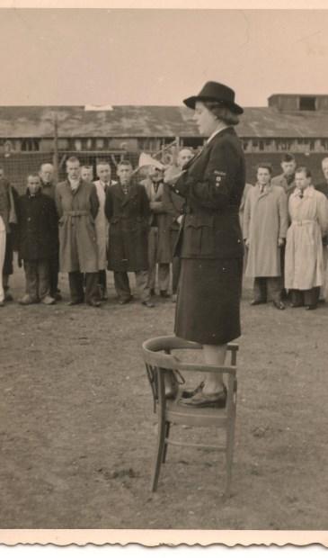 Loes Overeem spreekt direct na de oorlog staande op een stoel in Kamp Amersfoort de kampbewoners toe. (fotograaf onbekend/ Kamp Amersfoort)  © De Vierklank