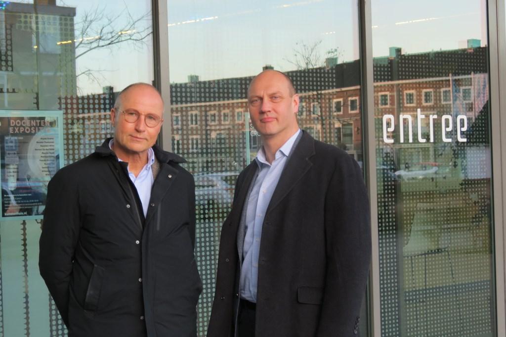 Jan Emmens (links) en Frank Heeneman bij de entree van Het Lichtruim waar in het glas de overkant weerspiegelt.  © De Vierklank