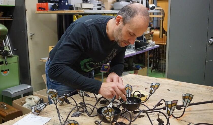 Reparateur Roger onderzoekt wat er mis is met de sierlamp van een bezoeker uit De Bilt.