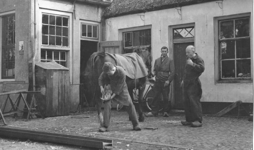 De jonge Geurt Vervat beslaat een paard, terwijl vader Goossen Vervat (rechts) toekijkt. (foto familie Vervat)