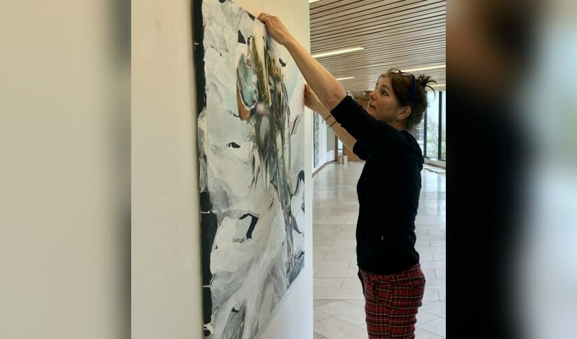 Lilian Oldenhof hangt een schilderij op van Kars Persoon in de traverse van het gemeentehuis. (foto Katrien Kroes)